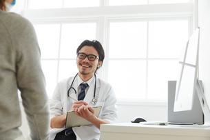 問診をしている笑顔の男性医師の写真素材 [FYI02998496]