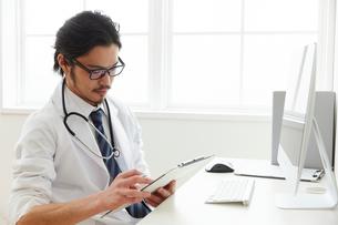 カルテに書き込みをしている男性医師の写真素材 [FYI02998497]