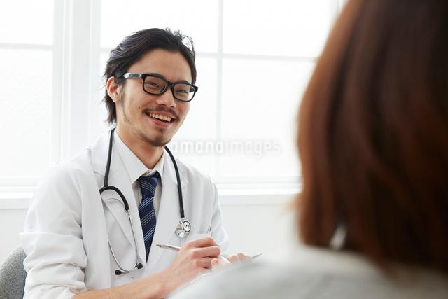 問診をしている笑顔の男性医師の写真素材 [FYI02998499]
