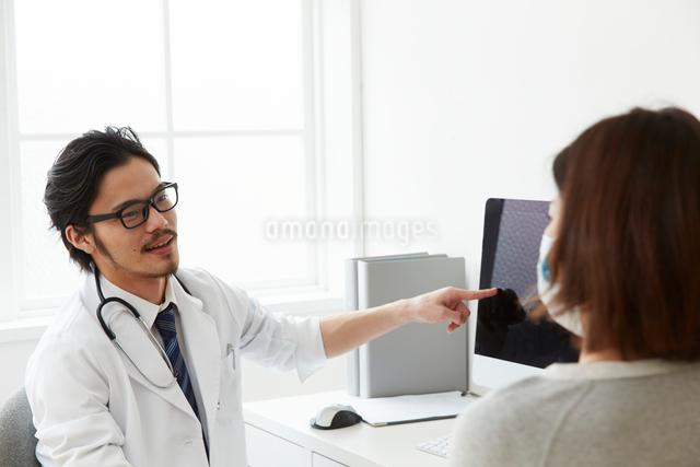 患者に説明をしている男性医師の写真素材 [FYI02998501]