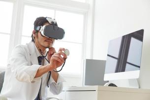 VRゴーグルをつけて聴診器を当てる男性医師の写真素材 [FYI02998502]