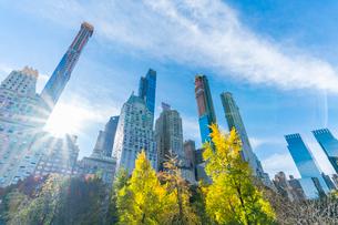 ミッドタウンマンハッタン摩天楼の間に輝く太陽に照らされるセントラルパークの紅葉。の写真素材 [FYI02999056]