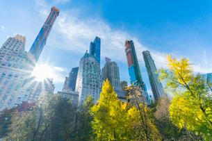 ミッドタウンマンハッタン摩天楼の間に輝く太陽に照らされるセントラルパークの紅葉。の写真素材 [FYI02999057]