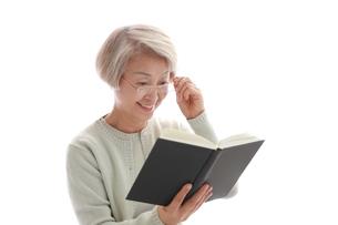 メガネを持って本を見ている老眼の老年女性の写真素材 [FYI02999368]