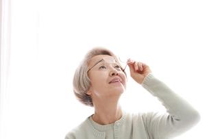 メガネを持っている老眼の老年女性の写真素材 [FYI02999369]