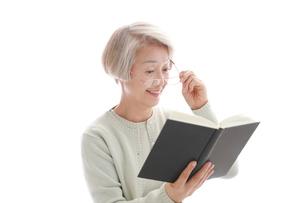 メガネを持って本を見ている老眼の老年女性の写真素材 [FYI02999370]