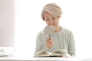 拡大鏡を持っている老年の女性の写真素材 [FYI02999378]
