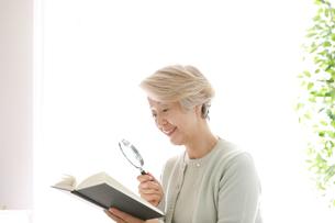 拡大鏡を持っている老年の女性の写真素材 [FYI02999379]