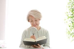 拡大鏡を持って本を見ている老年の女性の写真素材 [FYI02999380]