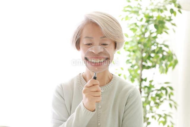 拡大鏡を持っている老年の女性の写真素材 [FYI02999382]