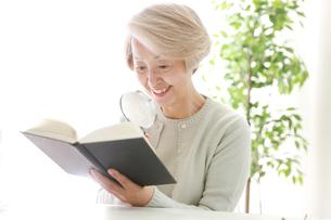拡大鏡で見る老年女性の写真素材 [FYI02999383]