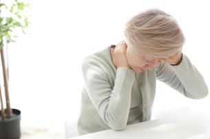 首の後ろの痛みを感じている中年の女性の写真素材 [FYI02999395]