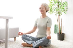 笑顔で室内でのヨガをしている老年の女性の写真素材 [FYI02999410]