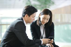 スマートフォンで営業活動しているビジネスマンの写真素材 [FYI02999415]