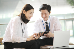 スマートフォンを見ながらビジネスしている会社員の写真素材 [FYI02999420]