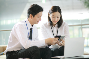 スマートフォンを手にするセールスマンと女性会社員の写真素材 [FYI02999423]