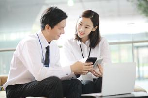 スマートフォンを見ながらビジネスしている会社員の写真素材 [FYI02999424]