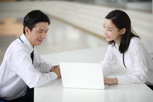ノートパソコンを使って相談しているビジネスウーマンの写真素材 [FYI02999430]