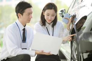 ノートパソコンを見ながら車のタイヤを指している女性のセールスウーマンの写真素材 [FYI02999444]