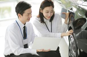 笑顔で自動車セールスしている女性のセールスウーマンの写真素材 [FYI02999446]