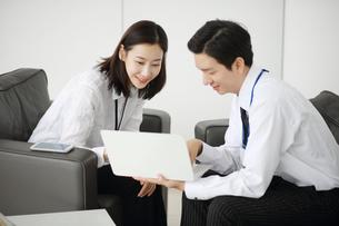 ノートパソコンを持って相談しているビジネスマンの写真素材 [FYI02999453]