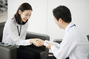 笑顔で握手しているセールスウーマンの写真素材 [FYI02999456]