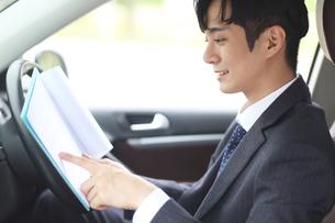 車で書類を見ているビジネスマンの写真素材 [FYI02999528]