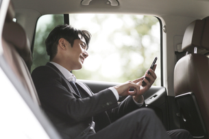 車の中でスマートフォンを操作しているビジネスマンの写真素材 [FYI02999529]
