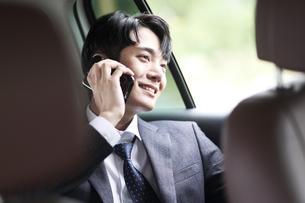 車の中で電話しているビジネスマンの写真素材 [FYI02999532]