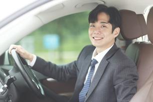 車の中で笑顔をしているビジネスマンの写真素材 [FYI02999541]