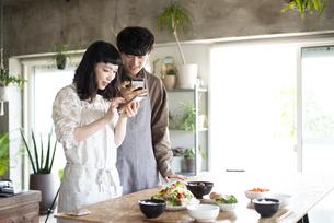 ご飯の写真をスマホで撮っているカップルの写真素材 [FYI03004004]