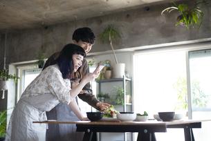 ご飯の写真をスマホで撮っているカップルの写真素材 [FYI03004032]