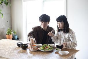 家でご飯を食べているカップルの写真素材 [FYI03004041]