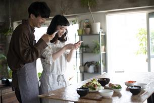 ご飯の写真をスマホで撮っているカップルの写真素材 [FYI03004042]