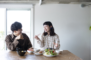 家でご飯を食べているカップルの写真素材 [FYI03004043]