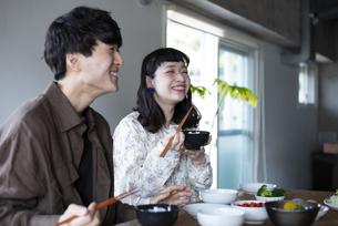 家でご飯を食べているカップルの写真素材 [FYI03004046]