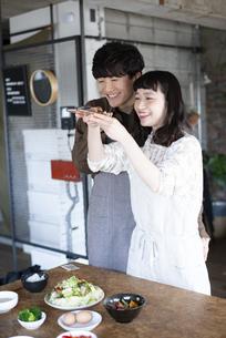 ご飯の写真をスマホで撮っているカップルの写真素材 [FYI03004050]