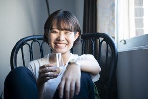 スパークリングウォーターを持って笑っている女性の写真素材 [FYI03004133]