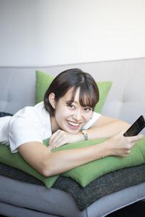 スマホを持ってソファに寝そべっている女性の写真素材 [FYI03004136]