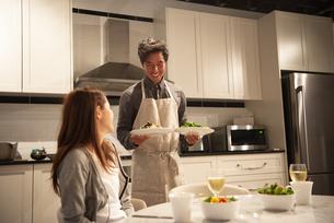 キッチンで料理を運んでいる男性の写真素材 [FYI03004162]