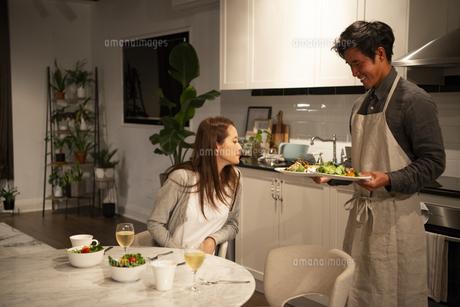 キッチンで料理を運んでいる男性の写真素材 [FYI03004164]