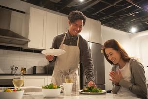 手料理を運んでいる男性と喜んでいる女性の写真素材 [FYI03004165]