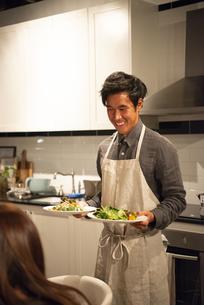 キッチンで料理を運んでいる男性の写真素材 [FYI03004166]