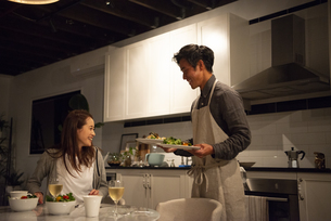 キッチンで料理を運んでいる男性の写真素材 [FYI03004167]