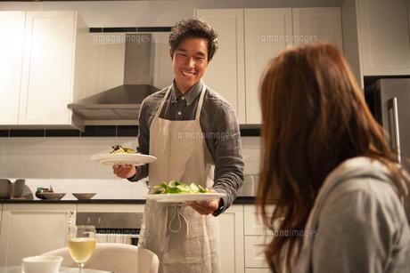 キッチンで料理を運んでいる男性の写真素材 [FYI03004168]