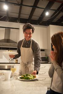キッチンで料理を運んでいる男性の写真素材 [FYI03004169]