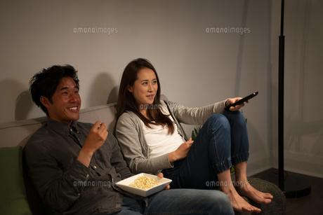 ポップコーンを食べながらテレビを見ているカップルの写真素材 [FYI03004170]