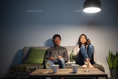 ポップコーンを食べながらテレビを見ているカップルの写真素材 [FYI03004171]