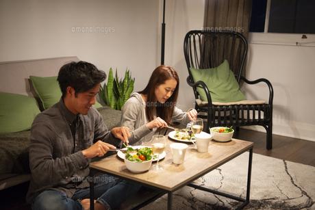 リビングで食事をしているカップルの写真素材 [FYI03004172]