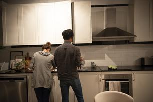 キッチンで一緒に家事をしているカップルの写真素材 [FYI03004174]